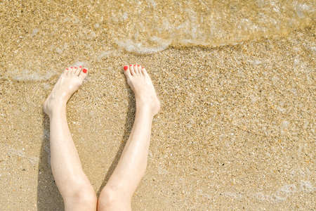 Top view of beautiful female feet with bright red pedicure on the sand of the beach. The sea wave washes womens feet. Relaxation and enjoyment during your seaside holiday. Copy space.