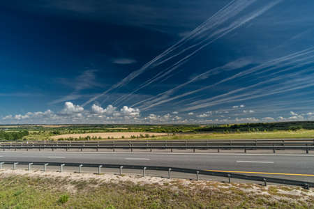 White traces of condensation of water vapor from airplanes over the motorway