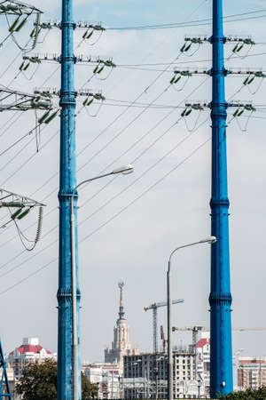 Two blue high voltage power line masts forming a natural framing against the backdrop of urban buildings. Wires and insulators