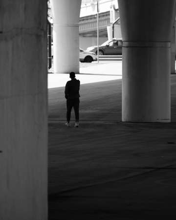 A human silhouette among giant concrete pillars under a road bridge. The concept of insignificance of a person in a huge metropolis. Contrast of light and shadow. Black and white image