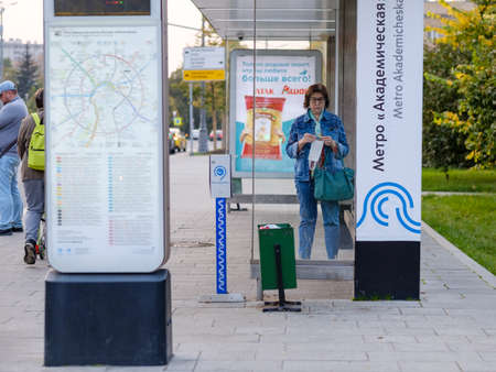 Moscow. Russia. September 25, 2020. An adult woman stands at a public transport stop with a medical mask in her hands Publikacyjne