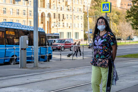 Moscow. Russia. October 4, 2020. An adult woman in a protective medical mask stands at a bus stop waiting for the bus.