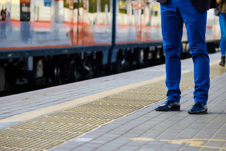Legs of a man in bright blue trousers and black leather shoes against the background of an arriving train