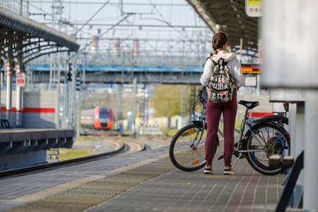 Moscow. Russia. October 4, 2020 A young girl with a bicycle and a backpack stands on the platform of a railway station