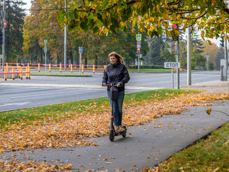 Moscow. Russia. October 11, 2020. Young woman rides an electric scooter on the sidewalk in a city park. Walk in the street on an autumn day. There are golden fallen leaves on the asphalt.