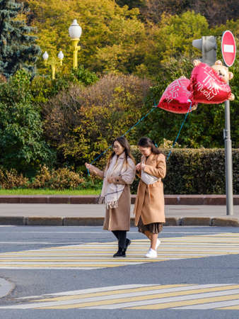 Moscow. Russia. October 11. A pair of girls in beige coats are holding red heart-shaped balloons. Autumn sunny day. Two LGBT girls and love.