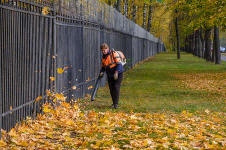 Moscow. Russia. October 11, 2020: A female utility worker uses a blower to remove fallen leaves on a lawn in a park. Yellow leaves are flying in the air. Autumn sunny day. Seasonal work concept. 新聞圖片