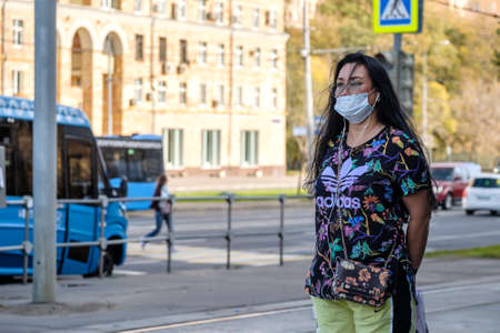 Moscow. Russia. October 4, 2020. An adult woman in a protective medical mask stands at a bus stop waiting for the bus. Sunny day in the city. The second wave of the coronavirus pandemic.