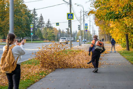 Moscow Russia. October 11, 2020 A utility worker uses a blower to remove fallen leaves in an alley in a park. Yellow leaves are flying. The girl behind takes a picture of the worker using a smartphone 新聞圖片