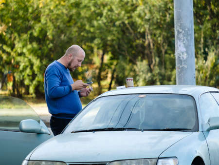 Moscow. Russia. On October 4, 2020. A bald man stands outside the open door of a car and smokes a cigarette while looking at his smartphone screen. Sunny autumn day. Tobacco smoke poisons the body. 新聞圖片