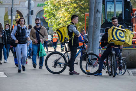 Moscow. Russia. October 4, 2020. A group of male delivery service men on bicycles stand on a city street. On the backs of the men are large yellow thermal bags.