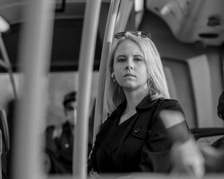 Moscow. Russia. September 29, 2020. A beautiful blonde girl with a pensive face stands in the cabin of the bus. Traveling around the city by public transport. Black and white photo.
