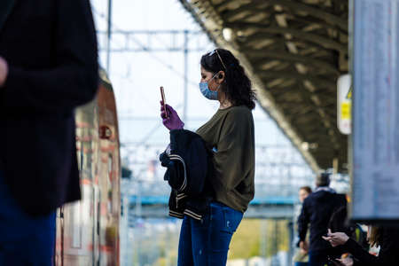 Moscow. Russia. October 4, 2020 A young girl in a protective mask stands on the platform of a metro station and looks with enthusiasm at a smartphone. Train carriages stop nearby.