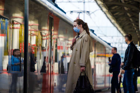 Moscow. Russia. October 4, 2020 A young woman wearing a protective medical mask stands on the platform of a metro station, waiting to board the train. The second wave of the coronavirus pandemic.
