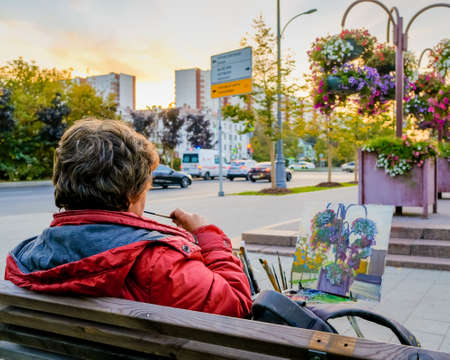 Moscow. Russia. October 1, 2020 A woman artist paints a picture with a brush and paints, sitting on a bench on a city street. Autumn evening. Flower beds with multi-colored flowers.