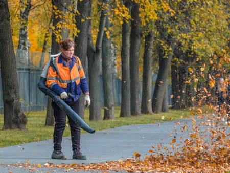 Moscow. Russia. October 11, 2020: A female utility worker uses a blower to remove fallen leaves in an alley in a park. Yellow leaves are flying in the air. Autumn sunny day. Seasonal work concept.