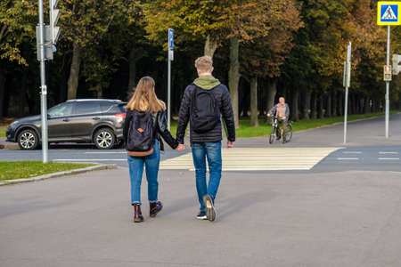Moscow, Russia. October 11, 2020. A full-length rear view of a couple of lovers crossing the road on a pedestrian crossing. Sunny day in autumn. The girl and the guy are holding hands. 新聞圖片
