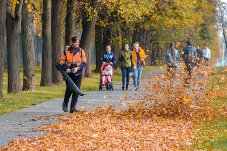 Moscow. Russia. October 11, 2020: A female utility worker uses a blower to remove fallen leaves in an alley in a park. Yellow leaves are flying in the air. Seasonal work concept. 新聞圖片