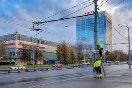 Moscow. Russia. October 19, 2020 Two workers in yellow uniforms assemble a road sign on a lamppost on a city street. A man stands on a ladder. Cloudy autumn day. Cars are driving along the road.