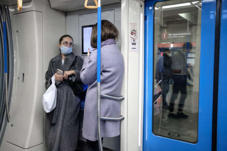 Moscow. Russia. October 19, 2020. A young woman in a subway car. The passenger has a protective medical mask on the face. Viral infection prevention measures. Social distance in public transport.