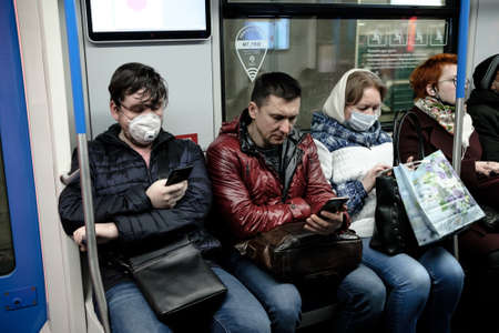 Moscow. Russia. October 19, 2020 A man in a subway car is looking at his smartphone with enthusiasm. The passenger has a protective medical mask on the face. Second wave of coronavirus. 新聞圖片