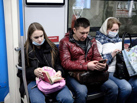 Moscow. Russia. October 19, 2020. A young girl in a subway car reads a book. The passenger has a protective medical mask on the face. Prevention of viral infections. Second wave of coronavirus. 新聞圖片