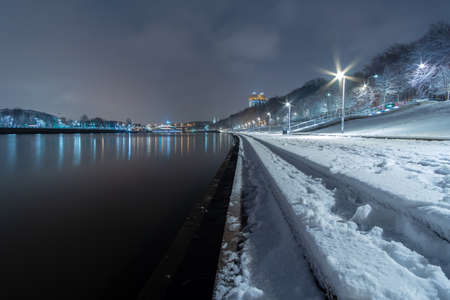 View of the Moskva River embankment at night in winter. The stone steps of the embankment, sidewalks and trees are covered with fresh snow. The backlight is on on the shore. Colorful city landscape.