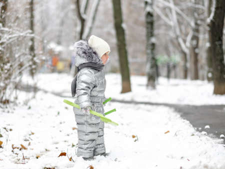 Happy child on a winter walk in the park. A funny little girl in a warm silver jumpsuit holds a toy shovel. First snowfall. Dry maple leaves peek out from under the snow. Blurred background.