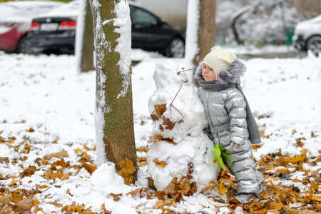 Happy child on a winter walk in the park. A funny girl in a silver jumpsuit holds a toy shovel and sculpts a snowman. Dry maple leaves peek out from under the newly fallen snow. Blurred background.