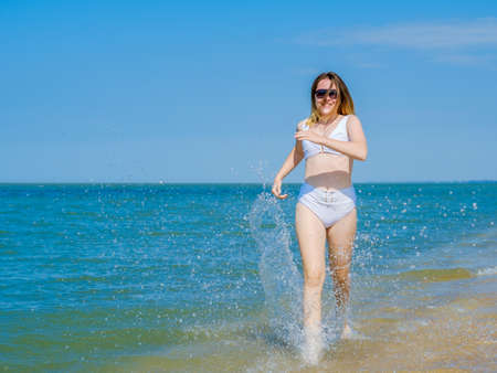 A young girl runs along the sandy sea beach along the surf. Splashes of sea water. The girl is wearing a white swimsuit and sunglasses. Freedom and carelessness. Outdoor fitness. Sunny day. Copy space