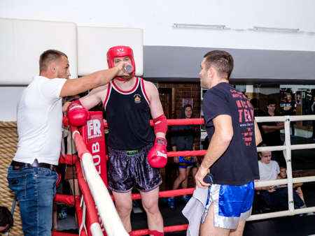 Moscow. Russia. September 13, 2020. A kickboxing fighter in uniform in the corner of the ring during the break. The seconds give instructions. Sports competitions in kickboxing and muay thai.
