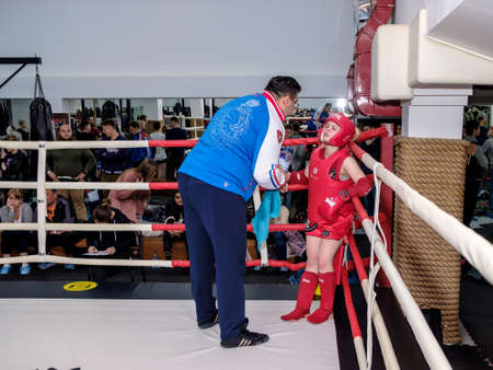 Moscow. Russia. September 13, 2020. Kickboxing fighter girl in uniform in the corner of the ring during the break. The seconds give instructions. Sports competitions in kickboxing and muay thai.