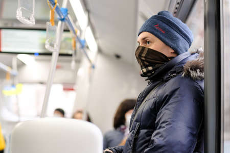 Moscow. Russia. March 26, 2021. A young man in a city bus with a scarf on his face as a protective mask. Prevention and protection against viral infections.