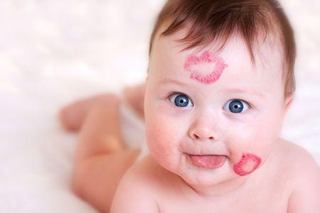 retrato del bebé con besos en su cara  Foto de archivo