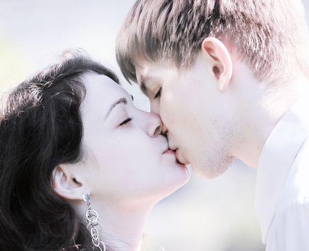 portrait of kissing couple in high key