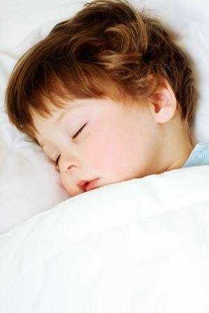 enfant qui dort: portrait d'enfant endormi dans le lit blanc Banque d'images