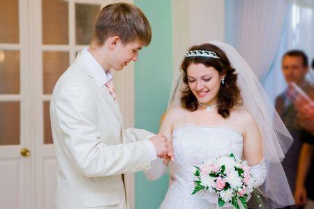 groom put on wedding ring on bride's finger Stock Photo - 4808565