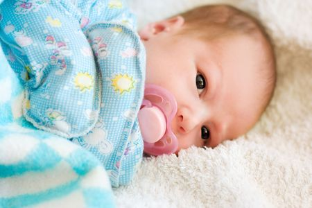 portrait of newborn baby with soother on white bedsheet Stock Photo - 4941077
