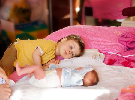 elder brother looks at newborn baby with interest Stock Photo - 4941075