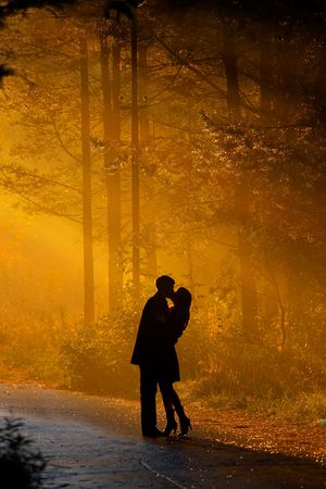hugs and kisses: beautiful shot of kissing couple in the sunlight Stock Photo