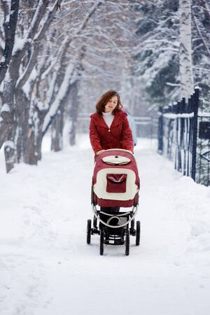 young mother with baby carriage in winter forest photo