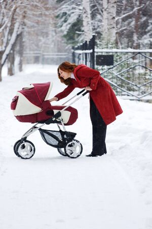 young mother with baby carriage in winter forest Stock Photo