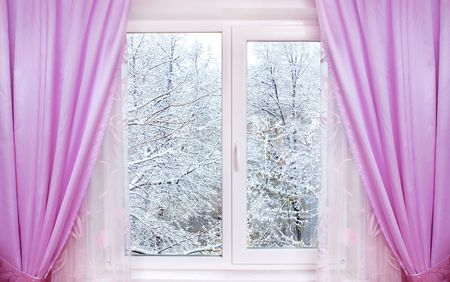 window with pink curtains and winter view behind it photo