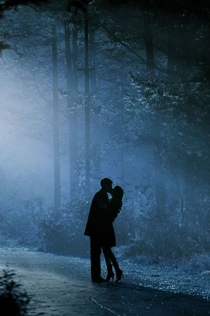 young couple kissing: beautiful shot of kissing couple in the sunlight Stock Photo