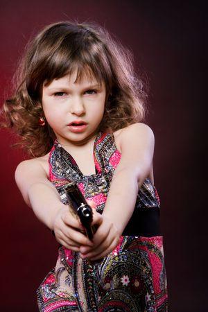 female assassin: portrait of little girl with pistol on black Stock Photo