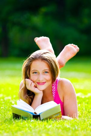 beautiful girl with book on the grass photo