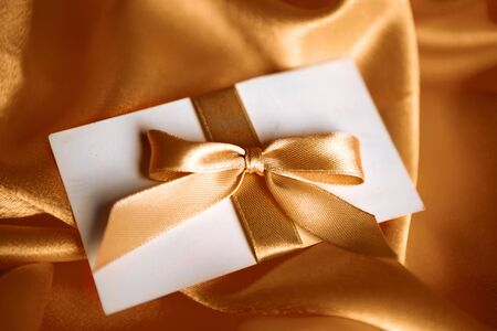 letter with golden ribbon on red satin Stock Photo