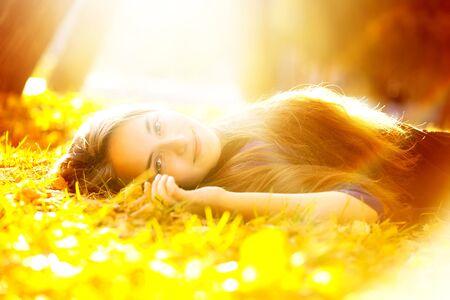 beautiful woman in sunbeam lying on the grass Stock Photo