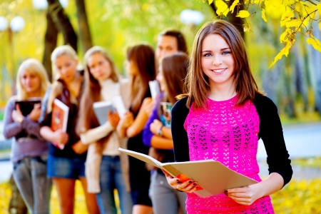 alone in crowd: many young girls in the autumn park with books Stock Photo