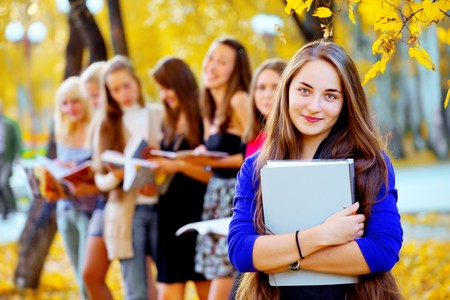 many young girls in the autumn park with books Stock Photo